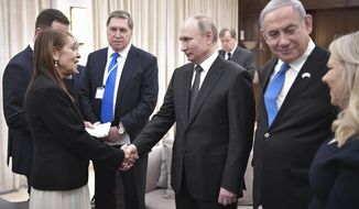 Russian President Vladimir Putin, center, shakes hands with Yaffa Issachar, mother of Israeli citizen Naama Issachar who is jailed in Russia for drug trafficking, during the meeting with Israeli Prime Minister Benjamin Netanyahu, 2nd right, in Tel-Aviv, Israel, Thursday, Jan. 23, 2020. Putin arrived to attend the World Holocaust Forum, which coincides with the 75th anniversary of the liberation of the Auschwitz death camp. (Aleksey Nikolskyi, Sputnik Kremlin Pool Photo via AP)