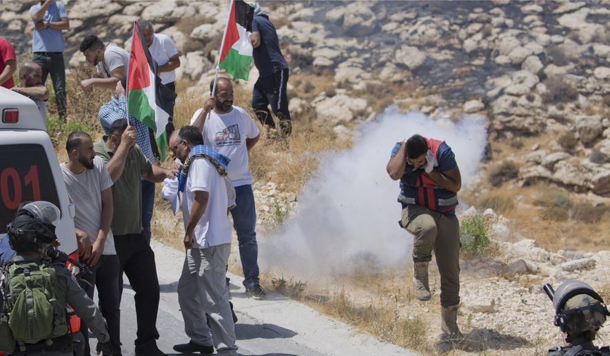 In this Aug. 16. 2019, file photo, Israeli border police disperse Palestinian, Israeli and foreign activists during a rally protesting a newly established settlement near the West Bank village of Kufr Malik, east of Ramallah. As President Donald Trump presented a Mideast plan favorable to Israel, Prime Minister Benjamin Netanyahu on Tuesday, Jan. 28, announced plans to move ahead with the potentially explosive annexation of large parts of the occupied West Bank, including dozens of Jewish settlements. (AP Photo/Nasser Nasser, File)