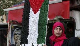 "A Palestinian woman holds a symbolic of the Palestine flag with Arabic words that read:""Palestine for us,"" as she attends a protest against the White House plan for ending the Israeli-Palestinian conflict, at Burj al-Barajneh refugee camp, south of Beirut, Lebanon, Wednesday, Jan. 29, 2020. At refugee camps across the country, Palestinians staged strikes, protests and sit-ins a day after U.S. President Donald trump revealed the long-awaited details of the plan, denouncing it as ridiculously lop-sided and saying it gives them no rights. (AP Photo/Hussein Malla)"