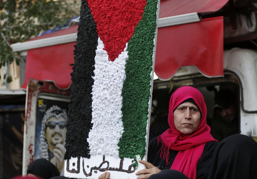"""A Palestinian woman holds a symbolic of the Palestine flag with Arabic words that read:""""Palestine for us,"""" as she attends a protest against the White House plan for ending the Israeli-Palestinian conflict, at Burj al-Barajneh refugee camp, south of Beirut, Lebanon, Wednesday, Jan. 29, 2020. At refugee camps across the country, Palestinians staged strikes, protests and sit-ins a day after U.S. President Donald trump revealed the long-awaited details of the plan, denouncing it as ridiculously lop-sided and saying it gives them no rights. (AP Photo/Hussein Malla)"""