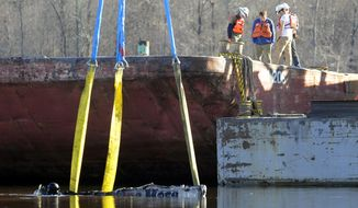 A diver works in the water as a crane attempts to lift the remains of a burned boat in Scottsboro, Ala., on Tuesday, Jan. 28, 2020, following a dock fire that killed eight people. Sunken in a creek that feeds into the Tennessee River, officials said the craft was one of about 35 that were engulfed in flames. (AP Photo/Jay Reeves)