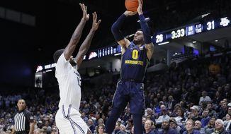 Marquette's Markus Howard (0) shoots over Xavier's  Naji Marshall (13) during the first half of an NCAA college basketball game Wednesday, Jan. 29, 2020, in Cincinnati. (AP Photo/John Minchillo)
