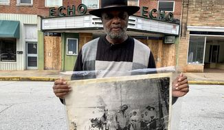 In this Monday, Jan. 13, 2020 photo, Rev. David Kennedy stands outside the Echo Theater holding a photo of his great uncle's lynching, in Laurens, S.C. Kennedy has fought for civil rights in South Carolina for decades. (AP Photo/Sarah Blake Morgan)