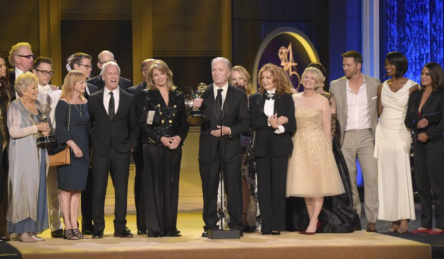 """FILE - This April 29, 2018 file photo shows Ken Corday, center, and the cast and crew of """"Days of Our Lives"""" accepting the award for outstanding drama series at the 45th annual Daytime Emmy Awards in Pasadena, Calif.  NBC announced that their longest running series has been renewed for a record 56th season. (Photo by Richard Shotwell/Invision/AP, File)"""