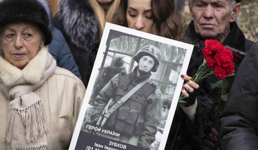 A relative holds photo of a soldier killed defending Donetsk airport in 2014-15 in a war conflict with Russia-backed separatists during a commemorating ceremony in Kyiv, Ukraine, Monday, Jan. 20, 2019. Ukraine has asked the Organization for Security and Cooperation in Europe to expand its monitoring mission in the country, Foreign Minister Vadym Prystaiko said Monday after a meeting with the organization's chairman. (Ukrainian Presidential Press Office via AP)