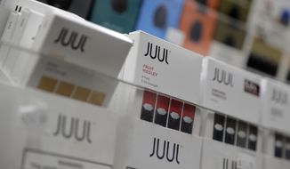 FILE - In this Dec. 20, 2018, file photo Juul products are displayed at a smoke shop in New York. The company that makes Marlboro cigarettes will take a $4.1 billion hit from its investment in Juul. Altria took a 35% stake in the e-cigarette company at the end of 2018 at a cost of almost $13 billion. The Richmond, Va.,  company on Thursday, Jan. 30, 2020 cited burgeoning legal cases that it expects to grow.  (AP Photo/Seth Wenig, File)