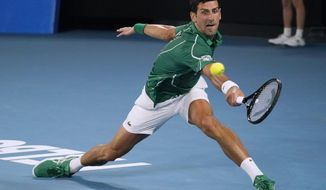 Serbia's Novak Djokovic makes a backhand return to Switzerland's Roger Federer during their semifinal match at the Australian Open tennis championship in Melbourne, Australia, Thursday, Jan. 30, 2020. (AP Photo/Lee Jin-man)