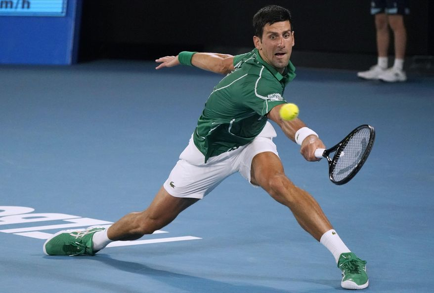 Serbia's Novak Djokovic makes a backhand return to Switzerland's Roger Federer during their semifinal match at the Australian Open tennis championship in Melbourne, Australia, Thursday, Jan. 30, 2020. (AP Photo/Lee Jin-man)