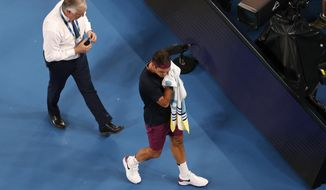 Switzerland's Roger Federer leaves the court for medical time out after the first set of his semifinal against Serbia's Novak Djokovic at the Australian Open tennis championship in Melbourne, Australia, Thursday, Jan. 30, 2020. (AP Photo/Andy Wong)