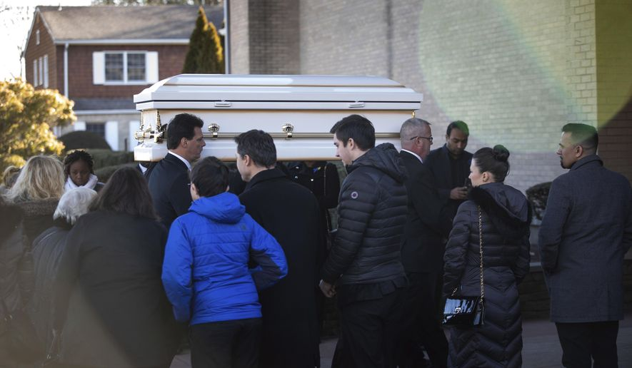 Pallbearers carry the casket into the funeral service for 8-year-old Thomas Valva at St. Elizabeth's Church on Thursday, Jan. 30, 2020, in Melville, N.Y. The boy's father Michael Valva, a New York City police officer, and his fiancee, Angela Pollina, are being charged with Thomas's death. (AP Photo/Kevin Hagen).