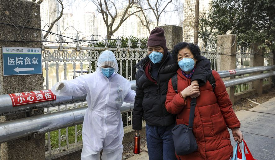 A medical worker in a protective suit helps a couple outside a hospital in Wuhan in central China's Hubei Province, Thursday, Jan. 30, 2020. China counted 170 deaths from a new virus Thursday and more countries reported infections, including some spread locally, as foreign evacuees from China's worst-hit region returned home to medical observation and even isolation. (Chinatopix via AP)