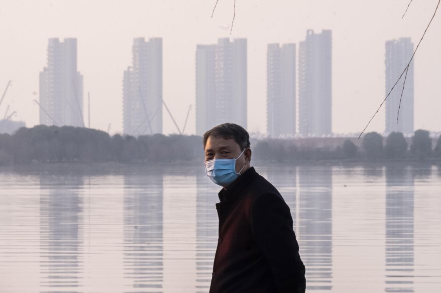 A man wears a face mask as he stands along the waterfront in Wuhan in central China's Hubei Province, Thursday, Jan. 30, 2020. China counted 170 deaths from a new virus Thursday and more countries reported infections, including some spread locally, as foreign evacuees from China's worst-hit region returned home to medical observation and even isolation. (AP Photo/Arek Rataj)