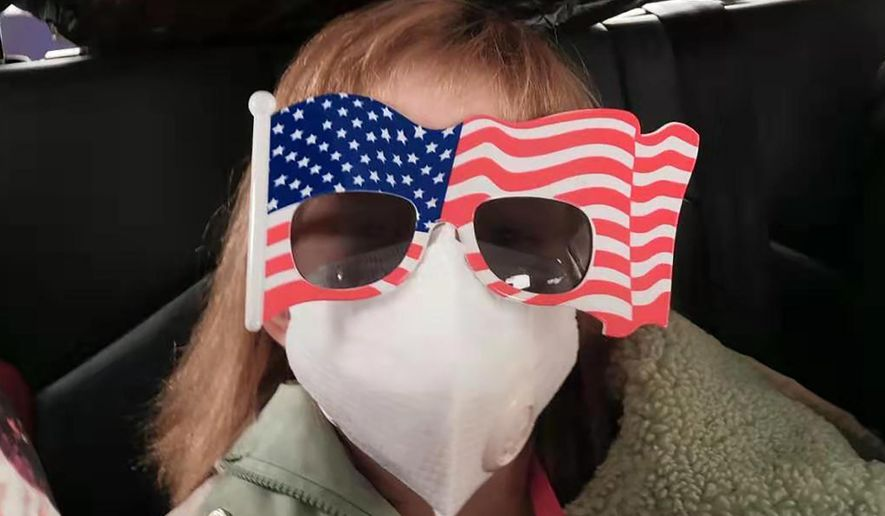 In this Tuesday, Jan. 28, 2020, file photo, Hermoine Dickey, 8, rides in a car on her way to Wuhan Tiange International Airport for a U.S. evacuation flight. Face masks are in short supply in parts of the world as people try to stop the spread of a new virus from China. Health officials recommend strap-on medical masks for people being evaluated for the new virus, their household members and caregivers. (Priscilla Dickey via AP, File) **FILE**