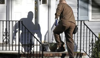 FILE - In this Nov. 26, 2019, file photo a UPS man delivers a package to a residence in North Andover, Mass. United Parcel Service Inc. reports financial results on Thursday, Jan. 30, 2020. (AP Photo/Elise Amendola, File)