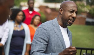 Rev. Raphael G. Warnock, pastor of Ebenezer Baptist Church, right, speaks during a press conference after Confederate flags were found on the church's premises in Atlanta, July 30, 2015. Warnock announced his campaign for the U.S. Senate on Thursday, Jan. 30, 2020 challenging recently appointed Republican Kelly Loeffler. (AP Photo/David Goldman, File)  ** FILE **
