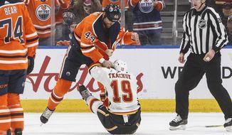 Calgary Flames' Matthew Tkachuk (19) and Edmonton Oilers' Zack Kassian (44) fight during the first period of an NHL hockey game Wednesday, Jan. 29, 2020, in Edmonton, Alberta. (Jason Franson/The Canadian Press via AP)