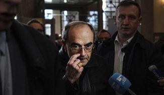 FILE - In this Nov.28, 2019 file photo, French Cardinal Philippe Barbarin, center, arrives at the Lyon courtroom, central France, for his appeal trial in Lyon. A French appeals court has acquitted Thursday, Jan.30, 2020 the French cardinal Philippe Barbarin of covering up the sexual abuse of minors in his flock. (AP Photo/Laurent Cipriani, File)