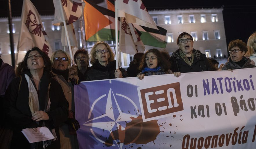 """Supporters of the Greek Communist Party hold a banner as they protest outside the Greek parliament in central Athens, against the Greek -US expanded defense agreement on Thursday, Jan. 30, 2020. The banner reads in Greek """"NATO Out"""". Greece's parliament is set to ratify an agreement with the United States for a major expansion of military cooperation as it faces an escalation of tensions with neighboring Turkey. (AP Photo/Petros Giannakouris)"""