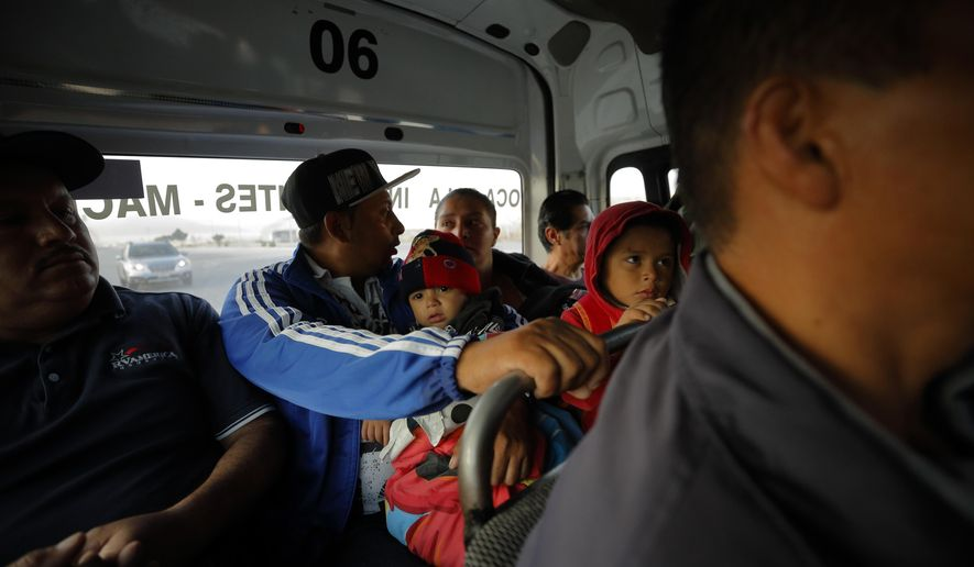 In this July 10, 2019, photo, Juan Carlos Perla, center, talks to his wife, Ruth Aracely Monroy, center right, as they take a bus from their home in Tijuana, Mexico, for an asylum hearing in San Diego. The Perla family of El Salvador has slipped into a daily rhythm in Mexico while they wait for the U.S. to decide if they will win asylum. (AP Photo/Gregory Bull)