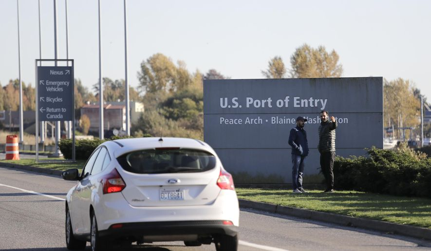 FILE - In this Oct. 9, 2019, file photo, pedestrians take a photo at an entry sign as traffic enters the United States from Canada at the Peace Arch Border Crossing in Blaine, Wash. U.S. Rep. Pramila Jayapal said Thursday, Jan. 30, 2020, she is working to authenticate an apparently leaked document showing that Customs and Border Protection agents on the U.S.-Canada border in Washington state were in fact ordered to detain Iranian and Iranian-American travelers early this month, despite initial agency denials. (AP Photo/Elaine Thompson, File)