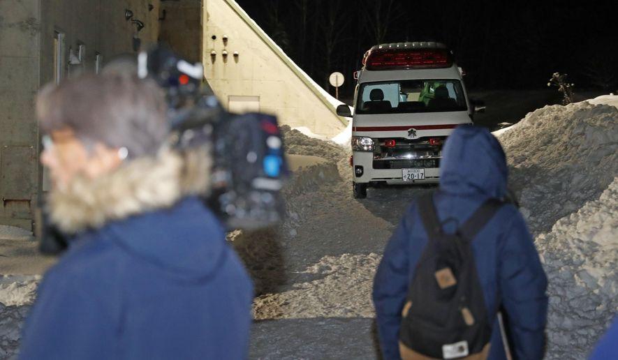 An ambulance waits as journalists, foreground, gather at the Tomamu ski resort in Shimukappu village, central Hokkaido, northern Japan, Thursday night, Jan. 30, 2020. An avalanche at the ski resort on Thursday hit a group of eight foreign skiers. (Yohei Fukai/Kyodo News via AP)