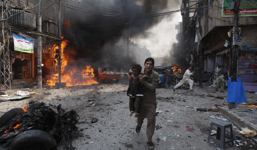 FILE - In this Sept. 29, 2013 file photo, a Pakistani man carrying a child rushes away from the site of a blast shortly after a car bomb exploded in Peshawar, Pakistan.  Terror attacks in Pakistan plummeted by more than 85% over the last decade. It's a welcome statistic for the country, but one that risks being overshadowed by international concern over its efforts to curb terror funding and lingering militant activity that could test any future peace agreement in Afghanistan. (AP Photo/Mohammad Sajjad, File)