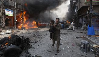 In this Sept. 29, 2013, file photo, a Pakistani man carrying a child rushes away from the site of a blast shortly after a car bomb exploded in Peshawar, Pakistan. (AP Photo/Mohammad Sajjad, File)