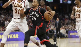 Toronto Raptors' Norman Powell (24) drives to the basket against Cleveland Cavaliers' John Henson (31) during the second half of an NBA basketball game Thursday, Jan. 30, 2020, in Cleveland. Toronto won 115-109. (AP Photo/Tony Dejak)