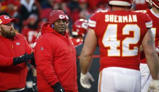 FILE - In this Jan. 20, 2019, file photo, Kansas City Chiefs offensive coordinator Eric Bieniemy watches players before the team's AFC championship NFL football game against the New England Patriots in Kansas City, Mo. The Chiefs have perhaps the most dynamic offense in the NFL and the San Francisco 49ers feature one of the stingiest defenses in the league. The men in charge of the units got interviews for head coaching but were passed over. (AP Photo/Charlie Riedel, File)