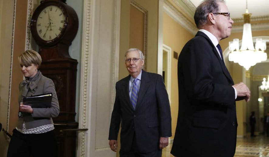 Senate Majority Leader Mitch McConnell, R-Ky., center, returns to the Senate chamber as Sen. Mike Braun, R-Ind., right, talks to the media during the impeachment trial of President Donald Trump at the Capitol Friday, Jan. 31, 2020, in Washington.  (AP Photo/Steve Helber)
