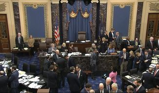In this image from video, Senate Majority Leader Mitch McConnell, R-Ky., lower right, talks with other GOP senators as the Senate is in a quorum call in the impeachment trial against President Donald Trump in the Senate at the U.S. Capitol in Washington, Friday, Jan. 31, 2020. (Senate Television via AP)