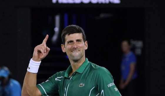 Serbia's Novak Djokovic celebrates after defeating Switzerland's Roger Federer in their semifinal match at the Australian Open tennis championship in Melbourne, Australia, Thursday, Jan. 30, 2020. (AP Photo/Lee Jin-man)