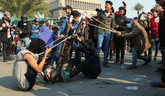 Anti-government protesters use a slingshot to fire a stone at security forces during clashes in Baghdad, Iraq, Thursday, Jan. 30, 2020. (AP Photo/Hadi Mizban)
