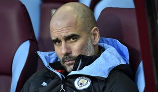 Manchester City's head coach Pep Guardiola looks out from the bench during warmup before the English Premier League soccer match between Aston Villa and Manchester City at Villa Park in Birmingham, England, Sunday, Jan. 12, 2020. (AP Photo/Rui Vieira)