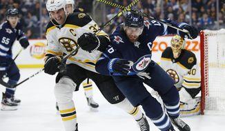 Winnipeg Jets' Blake Wheeler (26) and Boston Bruins' Zdeno Chara (33) chase the puck as goaltender Tuukka Rask (40) watches during the second period of an NHL hockey game Friday, Jan. 31, 2020, in Winnipeg, Manitoba. (John Woods/The Canadian Press via AP)