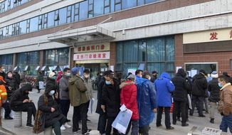 In this Friday, Jan. 31, 2020, photo, people line up outside a fever clinic at Wuhan Union Hospital in Wuhan in central China's Hubei Province. The United States on Friday declared a public health emergency and took drastic steps to significantly restrict entry into the country because of a new virus that hit China and has spread to other nations. (Chinatopix via AP)