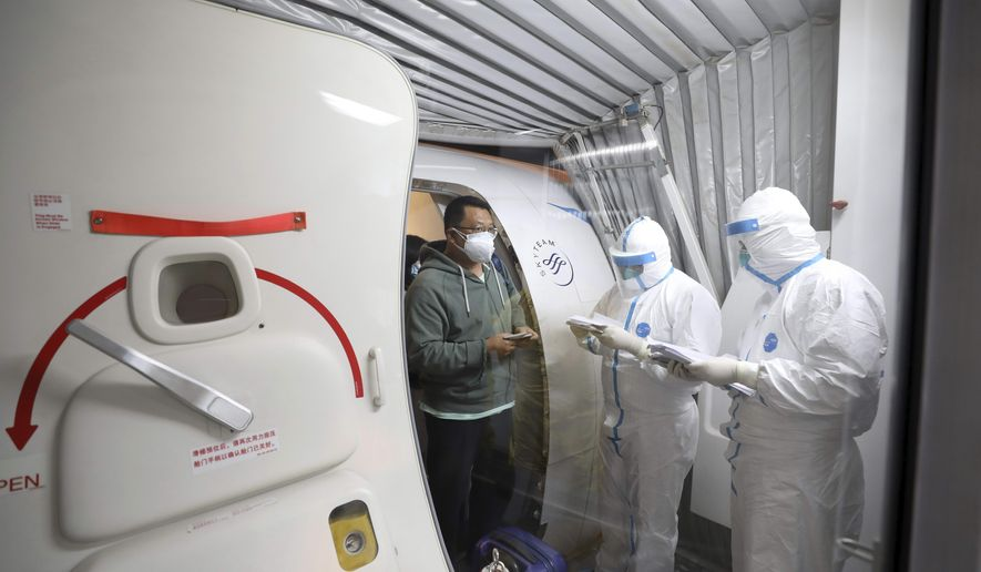Quarantine workers in protective suits check identity documents as tourists from the Wuhan area walk off of a chartered plane taking them home from Bangkok at Wuhan Tianhe International Airport in Wuhan in central China's Hubei Province, Friday, Jan. 31, 2020. A group of Chinese tourists who have been trapped in Thailand since Wuhan was locked down due to an outbreak of new virus returned to China on Friday. (Chinatopix via AP)