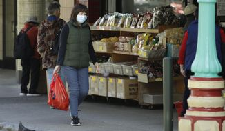 A masked shopper walks in the Chinatown district of San Francisco on Friday, Jan. 31, 2020. As China grapples with the growing coronavirus outbreak, Chinese people in California are encountering a cultural disconnect as they brace for a possible spread of the virus in their adopted homeland. (AP Photo/Ben Margot)