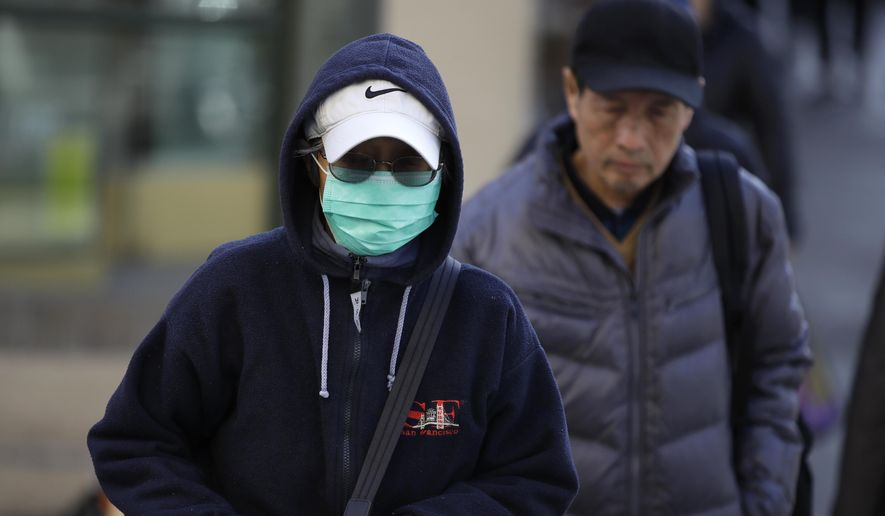 A masked woman walks a street in the Chinatown district of San Francisco on Friday, Jan. 31, 2020. As China grapples with the growing coronavirus outbreak, Chinese people in California are encountering a cultural disconnect as they brace for a possible spread of the virus in their adopted homeland. (AP Photo/Ben Margot)