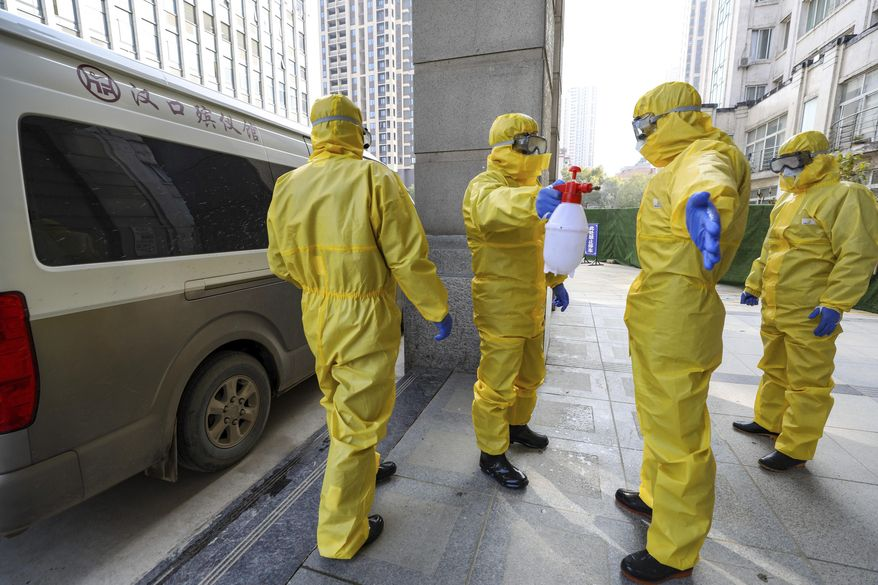 FILE - In this Jan. 30, 2020 file photo, funeral workers disinfect themselves after handling a virus victim in Wuhan in central China's Hubei Province, Thursday, Jan. 30, 2020. As global anxiety about a new virus rises, Chinese authorities are striving to keep 50 million people in cities at the center of the outbreak both isolated and fed in the biggest anti-disease effort ever attempted. (Chinatopix via AP, File)