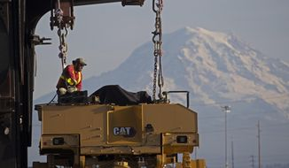FILE - In this Nov. 4, 2019, file photo a worker prepares a piece of Cat construction equipment made by Caterpillar to be lifted off a trailer at the Port of Tacoma in Tacoma, Wash. Caterpillar Inc. reports financial results Friday, Jan. 31, 2020. (AP Photo/Ted S. Warren, File)