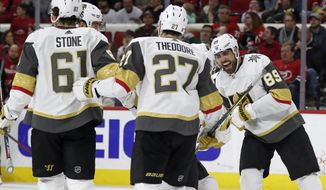 Vegas Golden Knights right wing Alex Tuch (89) celebrates with defenseman Shea Theodore (27) and right wing Mark Stone (61) following Tuch's goal against the Carolina Hurricanes during the third period of an NHL hockey game in Raleigh, N.C., Friday, Jan. 31, 2020. (AP Photo/Gerry Broome)