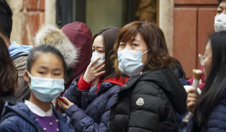 Chinese tourists wear masks in Rome, Friday, Jan. 31, 2020. Italy banned all flights coming from and going to China as European countries have stepped up their response to the new virus that has sickened thousands of people in China and reached 19 other countries. (AP Photo/Andrew Medichini)