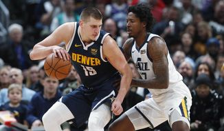 Denver Nuggets center Nikola Jokic, left, is defended by Utah Jazz center Ed Davis during the second half of an NBA basketball game Thursday, Jan. 30, 2020, in Denver. The Nuggets won 106-100. (AP Photo/David Zalubowski)