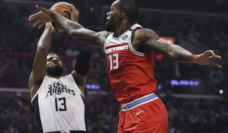 Los Angeles Clippers guard Paul George, left, shoots while Sacramento Kings center Dewayne Dedmon defends during the first half of an NBA basketball game in Los Angeles, Thursday, Jan. 30, 2020. (AP Photo/Kelvin Kuo)