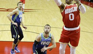 Houston Rockets guard Russell Westbrook (0) shoots as Dallas Mavericks guard J.J. Barea, center, and forward Ryan Broekhoff watch during the first half of an NBA basketball game Friday, Jan. 31, 2020, in Houston. (AP Photo/Eric Christian Smith)