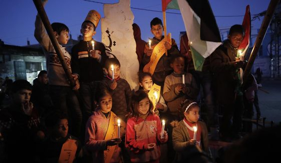 Protesters hold light candles as others wave their national flags during a protest against the Mideast plan announced by the U.S. President Donald Trump, at Jebaliya refugee camp, Gaza Strip, Thursday, Jan. 30, 2020. Trump's Mideast plan would create a disjointed Palestinian state with a capital on the outskirts of east Jerusalem, beyond the separation barrier built by Israel. The rest of the Jerusalem, including the Old City, would remain Israel's capital. (AP Photo/Adel Hana)