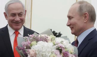 Russian President Vladimir Putin, right, prepares to greet Israeli Prime Minister Benjamin Netanyahu's wife Sara prior to talks with Israeli Prime Minister Benjamin Netanyahu in the Kremlin in Moscow, Russia, Thursday, Jan. 30, 2020. Netanyahu visited Moscow to discuss the U.S. Mideast peace plan with Putin and take an Israeli woman who had been jailed in Russia back home. (Maxim Shemetov/Pool Photo via AP)