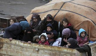 Syrians sit in the back of a truck as they flee the advance of the government forces in the province of Idlib, Syria, towards the Turkish border, Thursday, Jan. 30, 2020. Warplanes struck a town in a rebel-held enclave in northwestern Syria, killing several people, including some who were fleeing the attack, opposition activists and a rescue service said Thursday. The attack, believed to have been carried out by Russian warplanes backing a Syrian government offensive, also put a local hospital out of service, they said. (AP Photo/Ghaith Alsayed)