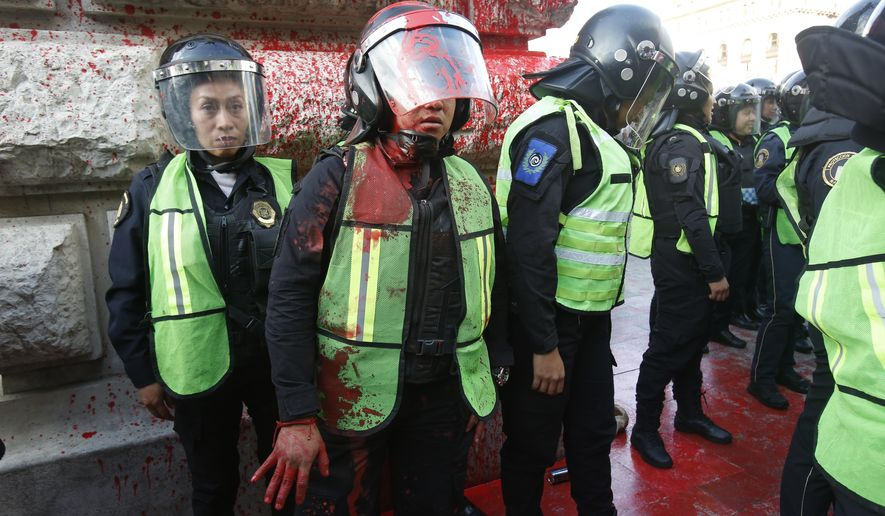 A female police officer covered in red paint stands by during a women's protest against the latest murder of two women, in Mexico City, Saturday, Jan. 25, 2020. In past weeks, two women activists, attorney Yunuen Lopez Sanchez and Isabel Cabanillas de la Torre, where murdered. (AP Photo/Ginnette Riquelme)